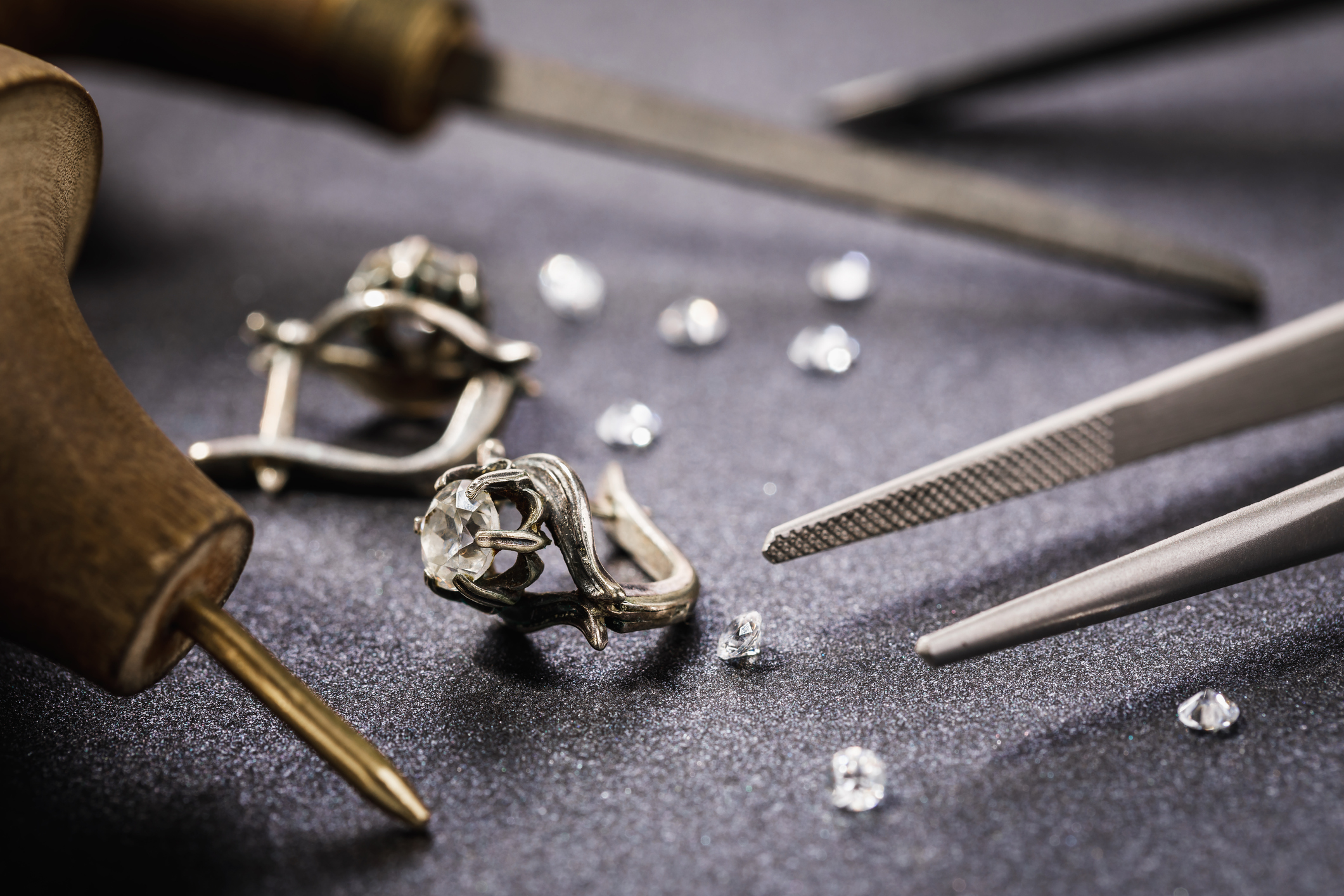 Earrings with a stone on the table, surrounded by jewelry repair tools